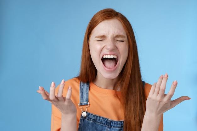 Boos verontwaardigd humeurig roodharige meisje schreeuwen klagen boos staan gehinderd hardop schreeuwen ogen sluiten luid schreeuwen handen zijwaarts opsteken ontzetting volledig ongeloof bedrogen voelen pijnlijk verraad