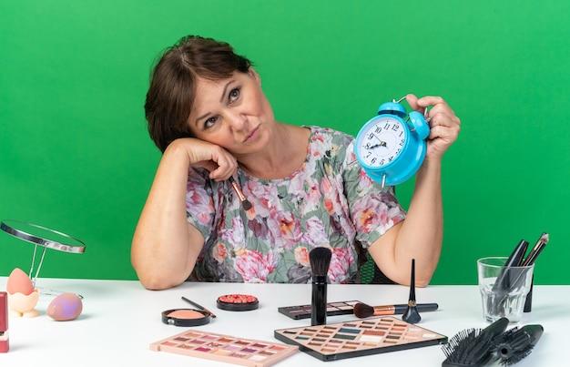 Boos volwassen blanke vrouw zittend aan tafel met make-up tools met wekker en make-up borstel geïsoleerd op groene muur met kopie ruimte opzoeken