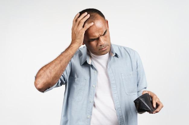 Boos volwassen man houden en kijken in zijn lege portemonnee op witte achtergrond. financiële crisis, faillissement, geen geld, slechte economie concept.