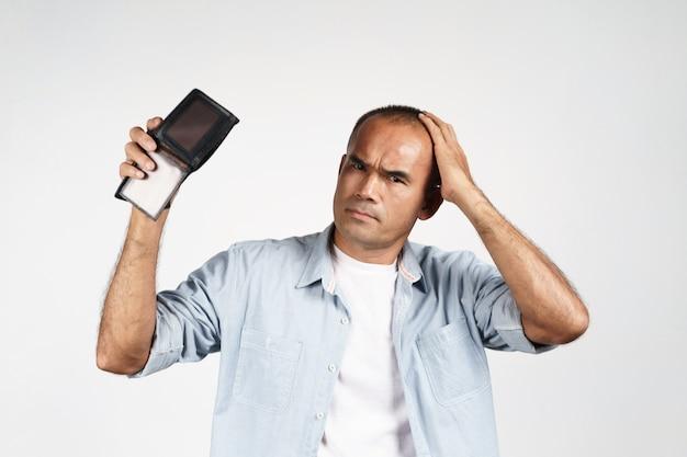 Boos volwassen man met zijn lege portemonnee op witte achtergrond. financiële crisis, faillissement, geen geld, slechte economie concept.