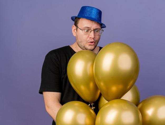 Boos volwassen slavische man in optische bril met blauwe feestmuts houdt en kijkt naar heliumballonnen