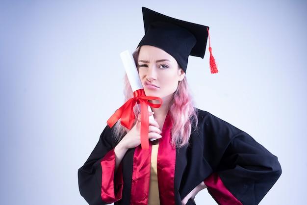 Boos vrouw in een bachelor-cap en mantel heeft haar afstudeercertificaat