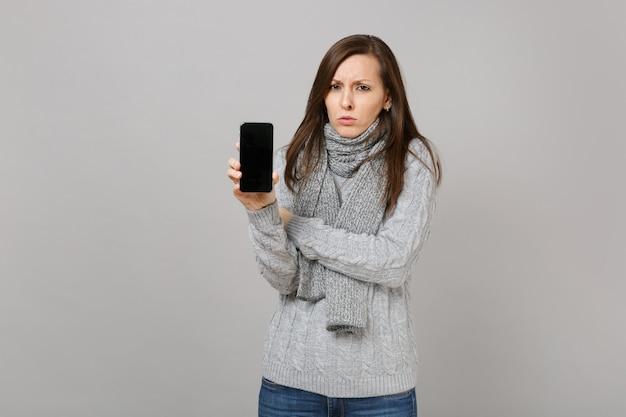 Boos vrouw in grijze trui, sjaal met mobiele telefoon met leeg leeg scherm geïsoleerd op een grijze achtergrond. gezonde mode levensstijl mensen oprechte emoties, koude seizoen concept. bespotten kopie ruimte.