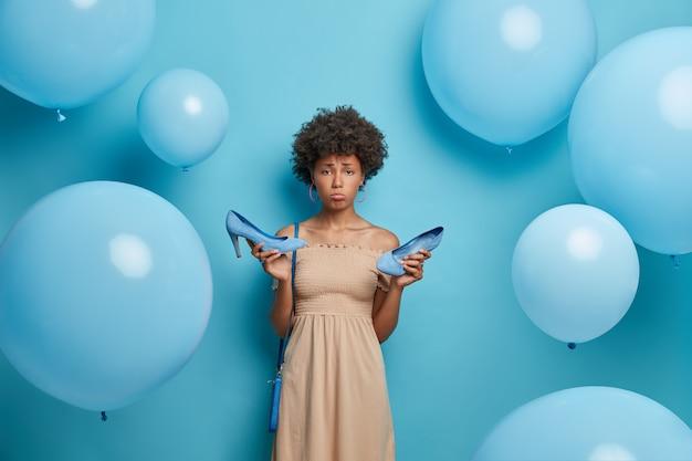 Boos vrouw kreeg eelt tijdens het dragen van schoenen met hoge hakken, draagt een cocktailjurk, heeft een slecht humeur, is moe na een feestje, geïsoleerd op een blauwe muur versierd met opgeblazen ballonnen. vrouwen kledingcollectie