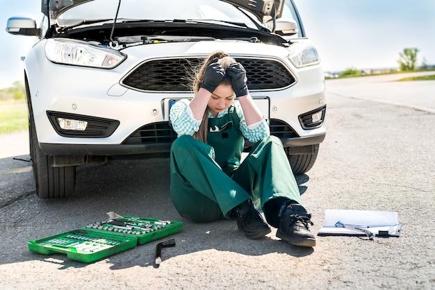 Boos vrouw monteur met verschillende instrumenten voor reparatie