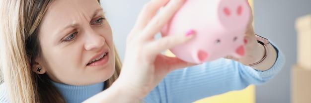 Boos vrouw schudt lege spaarpot close-up