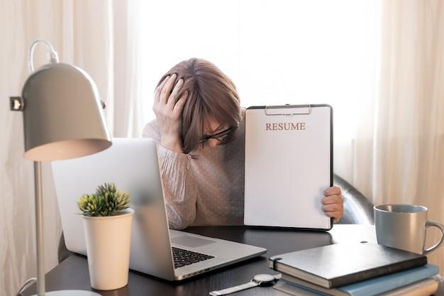 Boos vrouw sloot je gezicht van handen in de buurt van haar werkplek met laptop en hervat de applicatie.