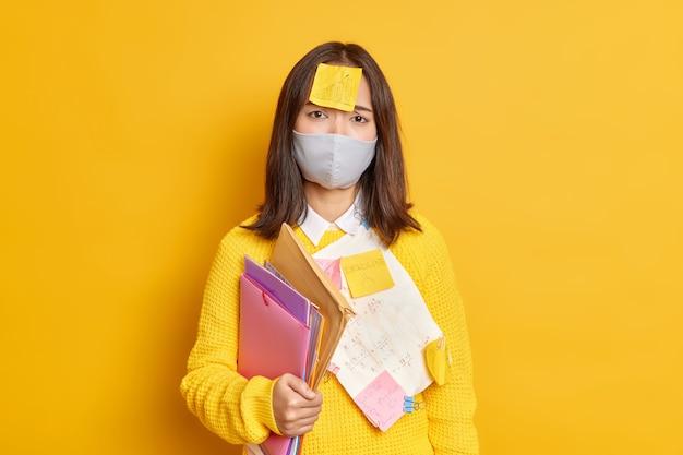 Boos vrouwelijke student werkt in de verte tijdens quarantaine draagt beschermend masker zelfklevende notitie met getekende afbeelding bereidt projectwerk voor ziet er helaas uit.