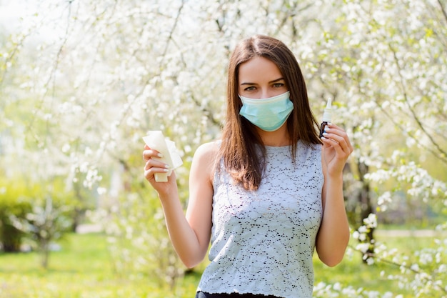 Boos wijfje dat allergie heeft die zich in bloeiende de lentetuin bevindt die medisch masker draagt
