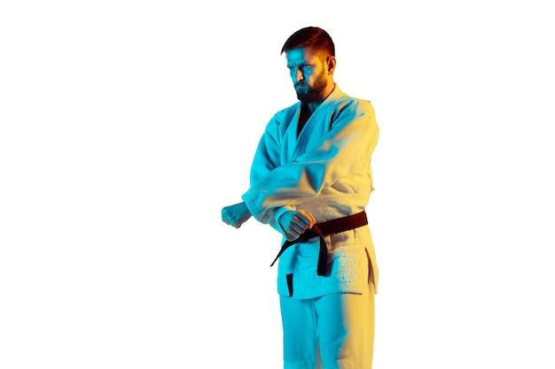 Boos. zelfverzekerde coach in kimono die hand-tot-hand-gevechten oefent