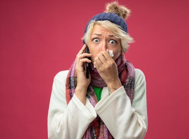 Boos zieke ongezonde vrouw met kort haar in warme sjaal en muts zich onwel voelen haar neus afvegen met servet bezorgd tijdens het praten op mobiele telefoon staande op roze achtergrond