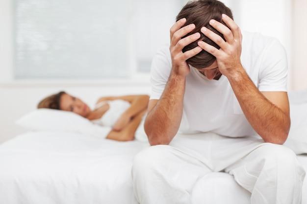 Boos zittende man en vrouw die op bed ligt