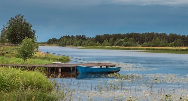 Boot bij een houten pier op de rivier in het dorp, in de korte noordelijke zomer