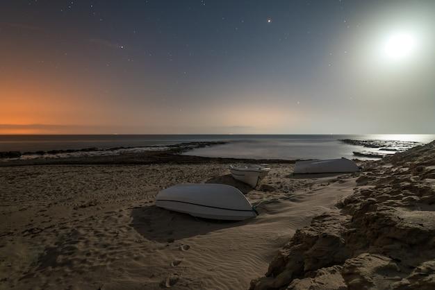 Boot die door de maan bij nacht op een strand van het zuiden van spanje wordt verlicht