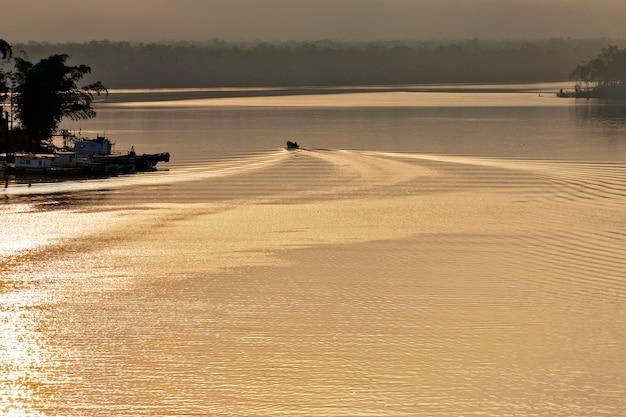 Boot die golven creëert in de gouden wateren van de rivier bij zonsopgang. itanhaem, staat sao paulo, brazilië
