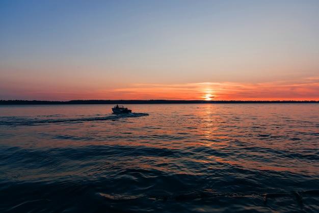 Boot drijft op watergolven op achtergrond van rode en blauwe zonsondergang met zon