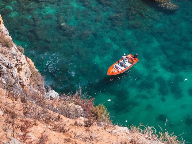 Boot drijvend op het water naast een klif