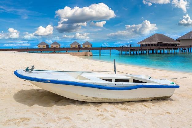 Boot en waterbungalows op tropisch eiland in de malediven