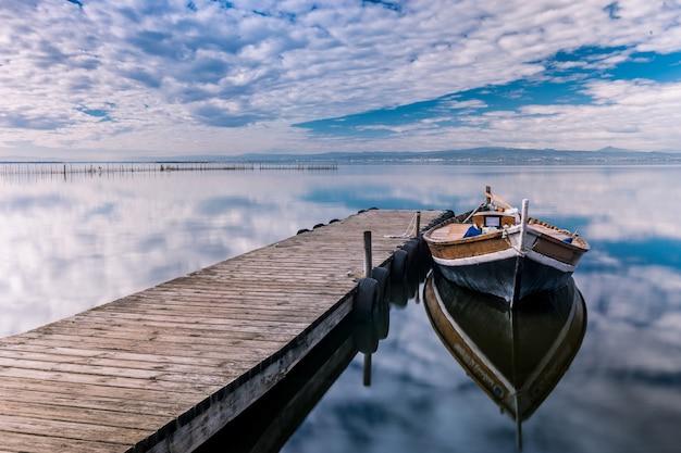 Boot geparkeerd in de buurt van de houten pier met reflecties in de zee onder de bewolkte hemel