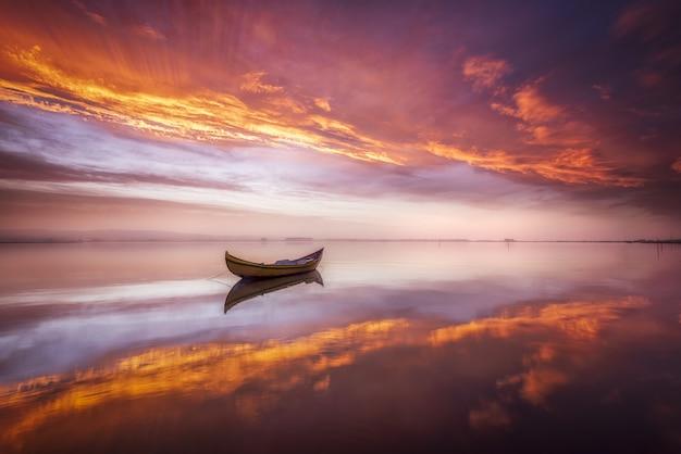 Boot in een meer bij zonsondergang