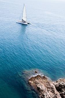 Boot in zee bij enkele rotsen