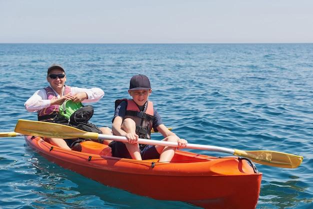 Boot kajakken in de buurt van kliffen op een zonnige dag. kajakken in een rustige baai. geweldig uitzicht. reizen, sport concept. levensstijl. een blije familie.