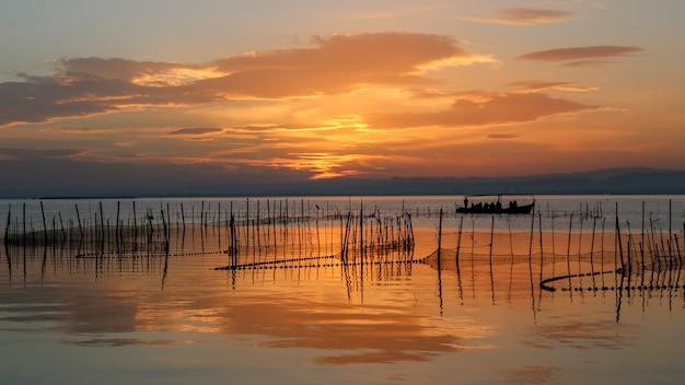 Boot met mensen in albufera van valencia bij zonsondergang.