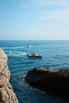 Boot met passagiers op zee, zomervakantie, jachttocht in het midden van rotsen en bergen, zeegezicht