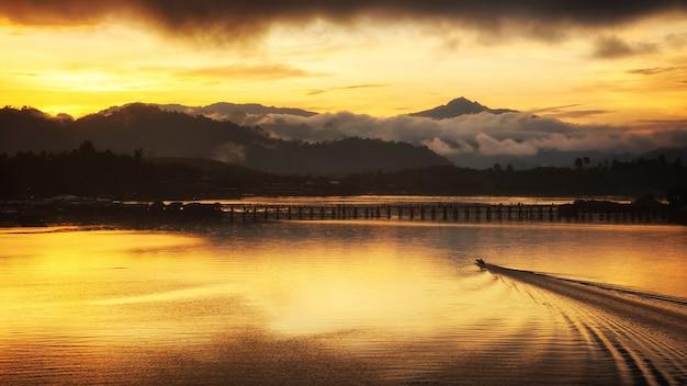 Boot naar houten brug bij zonsondergang