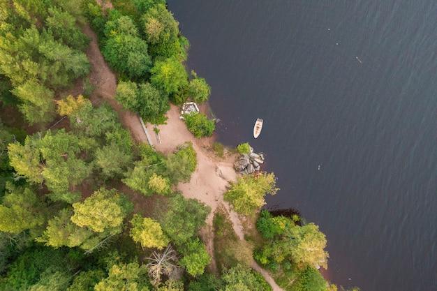 Boot op de rivier in de buurt van de bosbank. bovenste drone-weergave