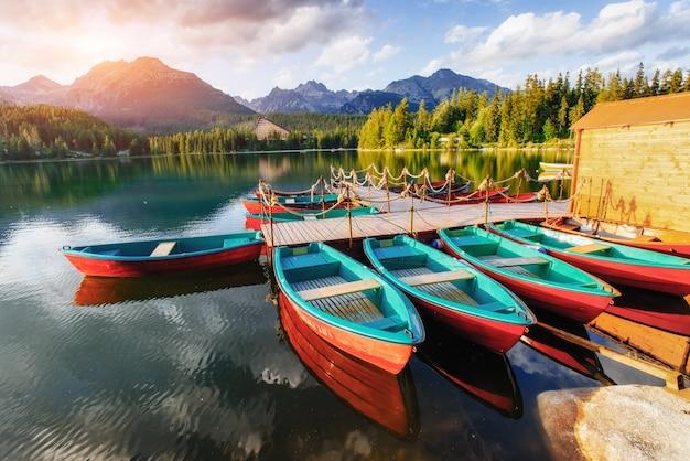 Boot op het dok dat door bergen bij zonsondergang wordt omringd.