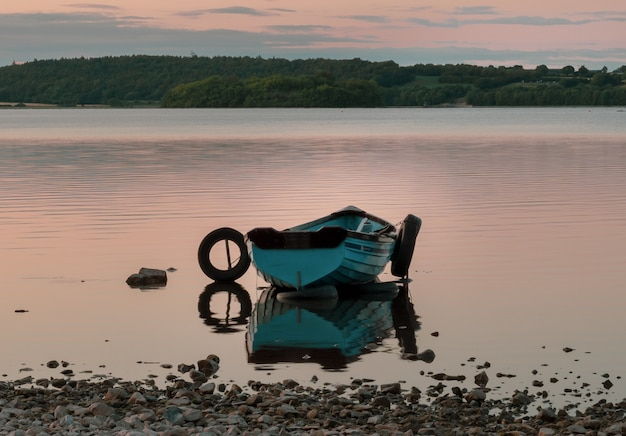 Boot op het meer in de buurt van de stad mullingar in ierland met weerspiegeling in het water bij zonsondergang