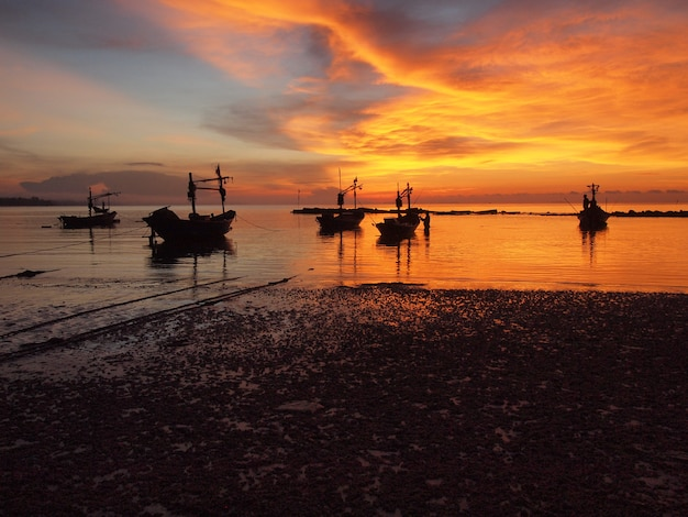 Boot op het strand bij zonsopgang in getijdetijd