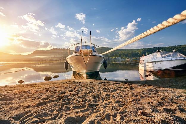 Boot op meer bij achtergrond van de dag van de zonsondergangzomer