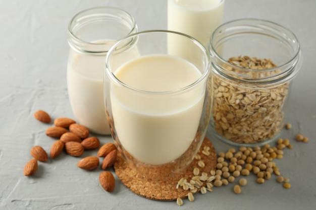 Bootle en glas verschillende soorten melk op grijs