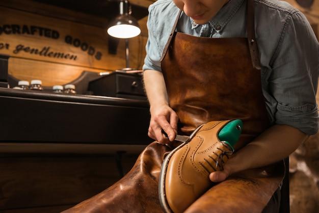 Bootmaker in workshop die schoenen maakt