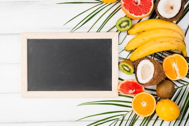 Bord dichtbij installatiebladeren met vers tropisch fruit