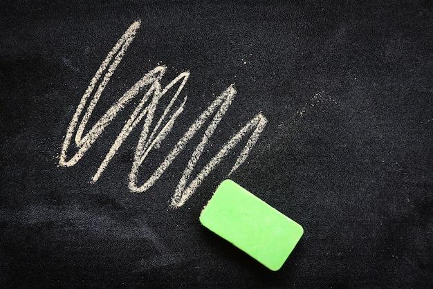 Bord donker of bord met horizontaal / bordtextuurkrijt en gom die voor onderwijs op schoolbordachtergrond schrijven en trekken
