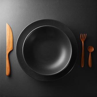 Bord en bestek op een zwarte tafel. voedselconcept