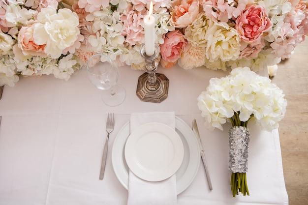 Bord en bruidsboeket op prachtig gedekte tafel versierd met bloemen