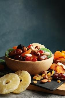 Bord en kommen met gedroogde vruchten en noten op grijze tafel