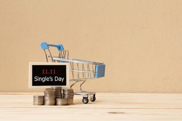 Bord en winkelwagentje met munten. online winkelen in china. verkoop concept voor één dag.