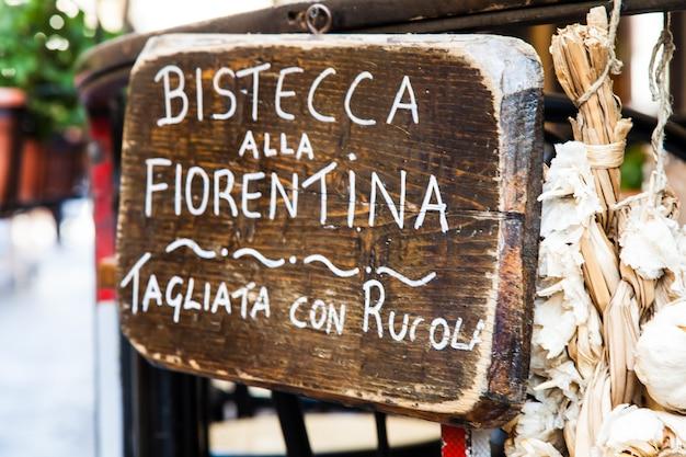 Bord gemaakt van hout met bistecca alla fiorentina (florence steak) woorden