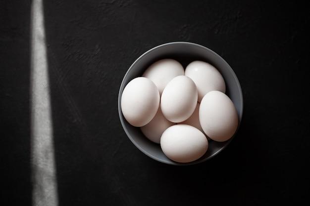 Bord gevuld met eierenmeer dan vier eierenfoto genomen op betonnen ondergrond grijze plaat en kippeneierende zonnestralen vallen in het frame