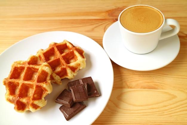 Bord met belgische wafels en blokjes pure chocolade met espressokoffie op de achtergrond