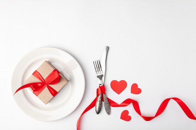 Bord met cadeau en bestek gebonden met een rode tape