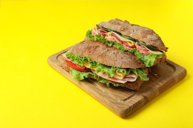 Bord met ciabatta sandwiches op gele achtergrond