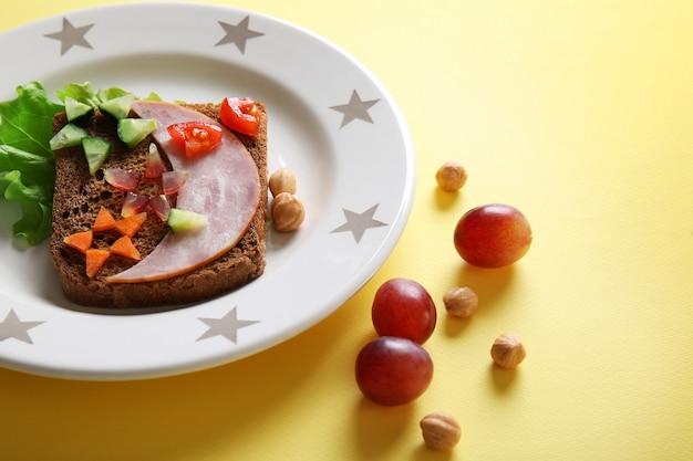 Bord met creatieve sandwich en druif op gele achtergrond