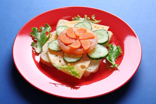 Bord met creatieve sandwich op blauwe achtergrond