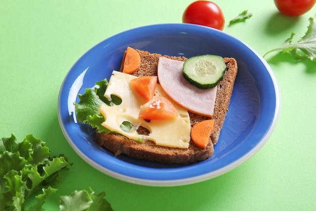 Bord met creatieve sandwich op groene achtergrond